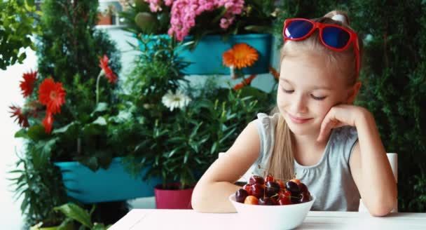 Portrait girl eating cherry and looking out distance