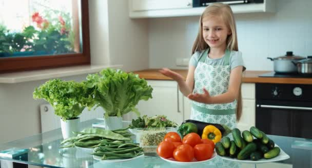 Mladá dívka šéfkuchař podporuje zeleniny. Dívka stojící vedle kuchyňského stolu a usmívá se na kameru. Palec nahoru. Ok