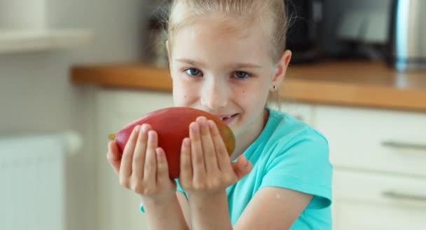 Lány mango szippantás és mosolyogva kamera. Gyermek kínál a nézők egy mangó gyümölcs. Mango gyümölcs elősegíti a gyermek