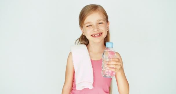 Dívka dítě sportovec zobrazeno láhev vody. Palec nahoru. Ok