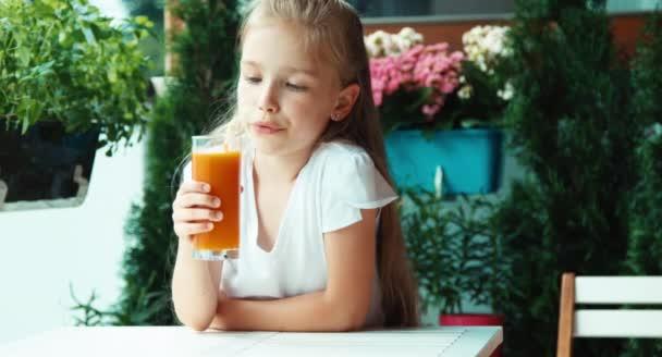 Porträt Mädchen trinkt Saft gegen die Blume und blickt in die Kamera