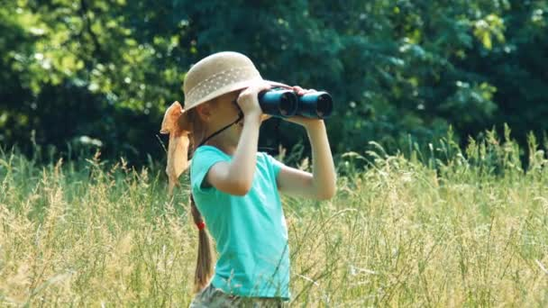 Closeup portrait girl naturalist explorer looking through binoculars at distance and smiling at camera. Zooming