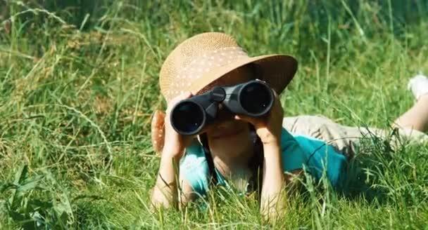 Vértes portré fiatal természettudós keresztül távcső figyelte a vadon élő állatok. Gyermek feküdt a fűben, és nevetve a kamera