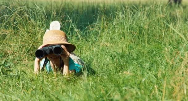 Young naturalist explorer with binoculars watching wildlife. Child lying on the grass