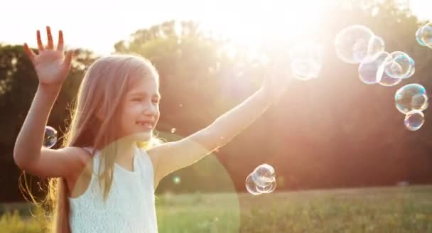 Girl catching soap bubbles in sunlight. Happy child laughing. Lens flare