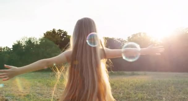 Girl spinning in the sunlight and soap bubbles. Lens flare. Child reaches for sunlight