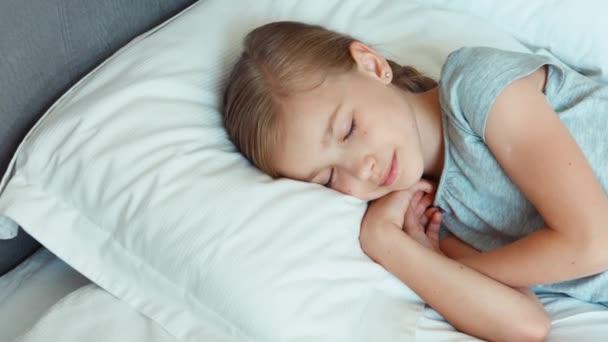 Dívka je v posteli a usmívá se. Zvětšení/zmenšení