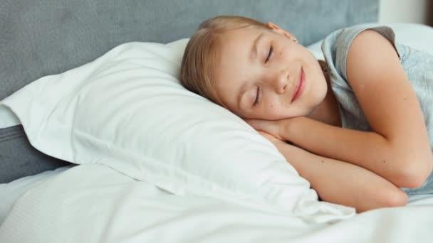 Vértes portré lány alszik egy ágyban, és mosolygott. Kicsinyítés/nagyítás