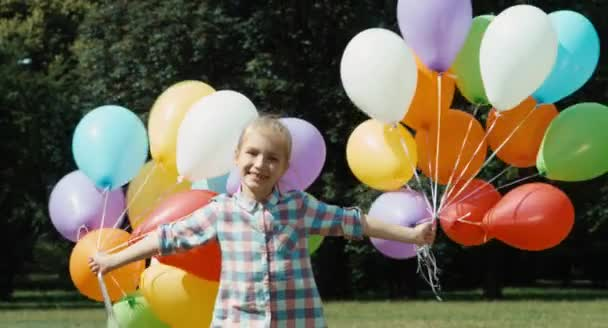 Portré nevető lány léggömbökkel a parkban