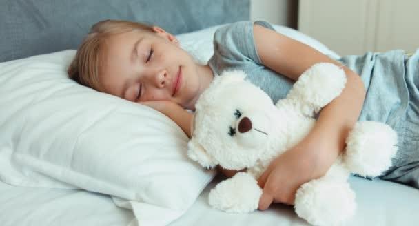 A lány alszik, és teddy medve átölelve egy ágy