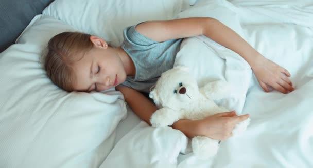 Portré lány 6-8 éves alszik az ágyban és átölelve játék mackó. Szemközti nézet