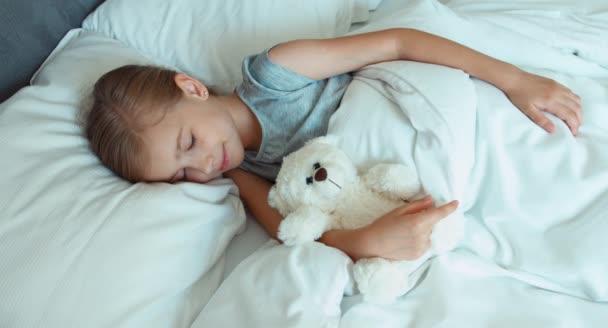 Portré lány 6-8 éves mackó ágyban alszik, és felébred. Szemközti nézet