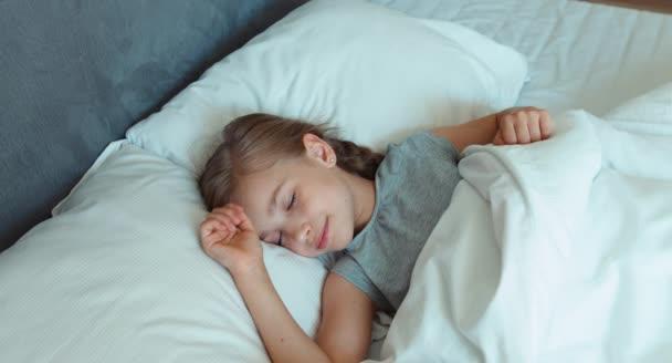 Portré lány 6-8 éves korig nyúlik egy ágyban, és felébred. Szemközti nézet