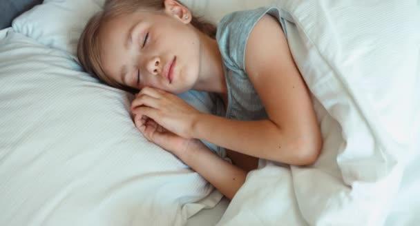 Vértes portré lány 6-8 éves alszik egy ágyban, és felébred. Szemközti nézet