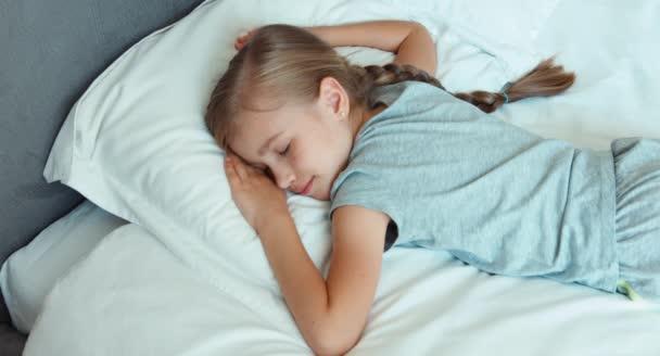 Dívka spí v posteli a usmívá se. Pohled shora