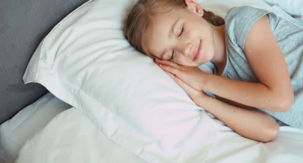 Dívka se probudí v posteli a usmívá se na kameru