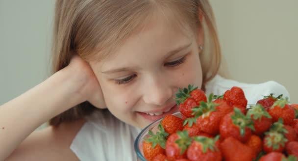 Extrémní portrét dívka objímá velký talíř jahod a směje se na kameru. Pohled shora
