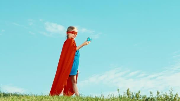 Erős Superhero lány gyermek védi a világ ellen, a kék ég. Szuper hős tartja kezében föld