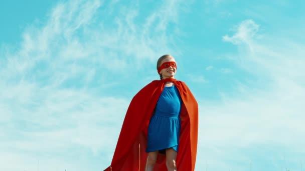 Superhero lány gyermek 7-8 éves védi a világ ellen, a kék ég