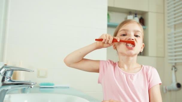 Zblízka portrétní dítě dívka 7-8 let čištění zubů v koupelně a při pohledu na fotoaparát