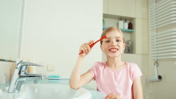 Portrait girl child 7-8 years old cleaning teeth in bathroom and looking at camera