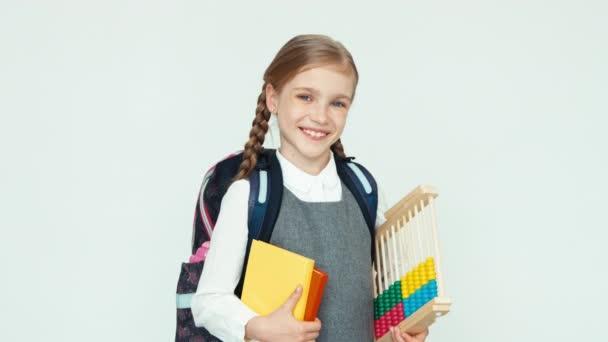 Portrét roztomilá školačka šťastné dítě 7-8 let s batoh drží abacus a knihy na bílém pozadí, usmívá se zuby na kameru