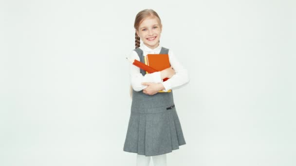 Cute happy schoolgirl child 7-8 years on white background hugging books and smiling. Girl holding books and big pencil