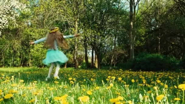 Aranyos lány 7-8 éves koszorú pitypang a fejét, spinning a parkban