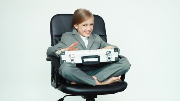 Business girl 7-8 years old with case and mobile phone on white background sitting on the chair