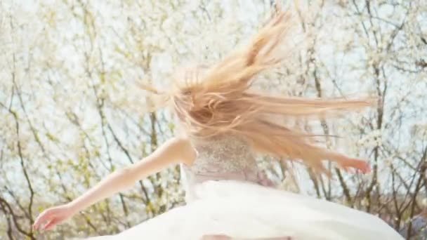 Cute blonde girl spinning in a dress on a background of blooming trees. Slow Motiona Sony A6300