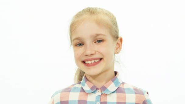 Portrait 7-8 years old girl in the shirt standing on the white background and smiling at camera