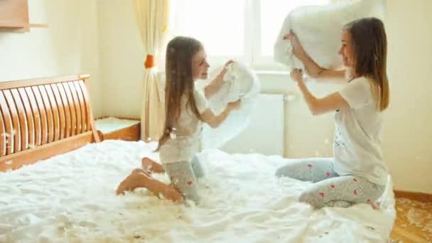 Lotta di cuscini sul letto. Madre e figlia di combattimento sul letto nella camera da letto soleggiata. Tra la peluria e piume. Vittoria di bambino