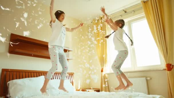 Happy daughter and mother jumping and spinning on the bed. Among the fluff and feathers