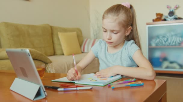 Child drawing in a notebook and looking at tablet pc