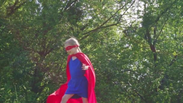 Boldog szuperhős a lány 7-8 éves futás és spinning a kék ég ellen. Slowmotion a Sony A6300