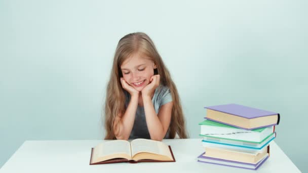 Portrait schoolgirl reading book at the table. On white background. Child smiling at camera and stretching