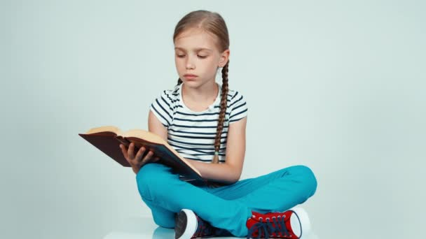 Portrait girl reading a book sitting on the floor and smiling at camera with teeth