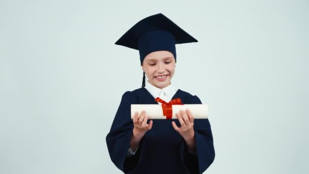 Portrait happy student graduate girl 7-8 years in mantle holding and rejoices her diploma. Child smiling with teeth on white