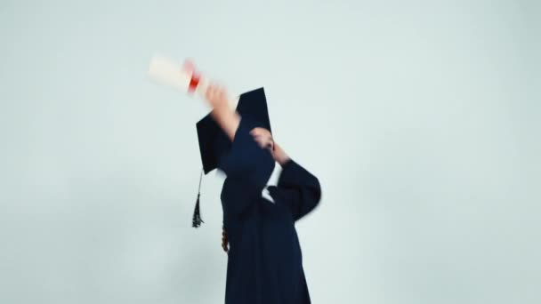 Happy student graduate girl 7-8 years child has diploma and dancing with it on white