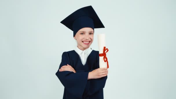Portrait happy student graduate girl 7-8 years in mantle holding her diploma and smiling with teeth on white