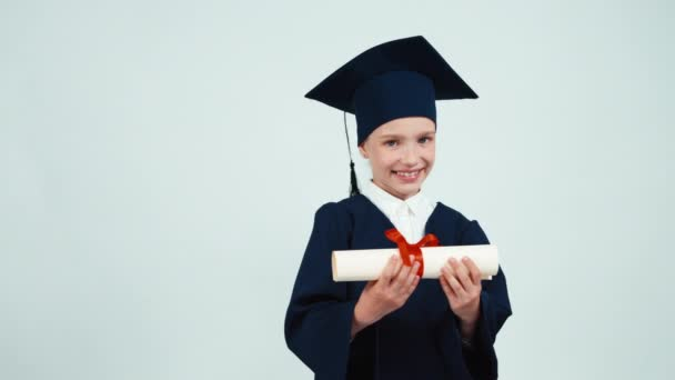 Portrait happy student graduate girl 7-8 years in mantle holding and rejoices her diploma on white