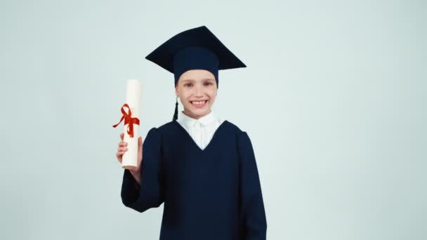 Happy graduate girl 7-8 years in the mantle and hat holding diploma and has power on white and smiling at camera