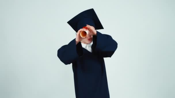 Child graduate looking through diploma at camera on white