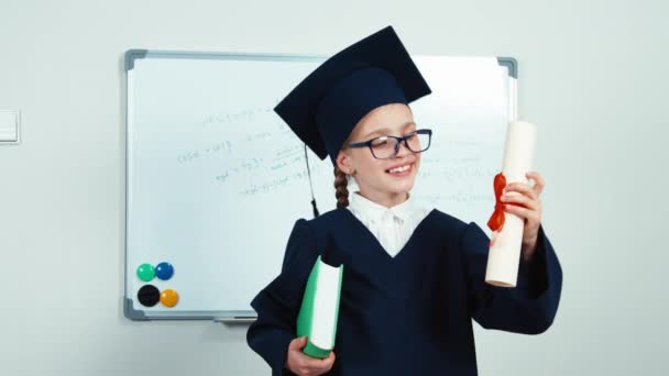 Graduate student 7-8 years in the mantle and hat. Child holding diploma and book. Girl smiling with teeth near whiteboard. Slider