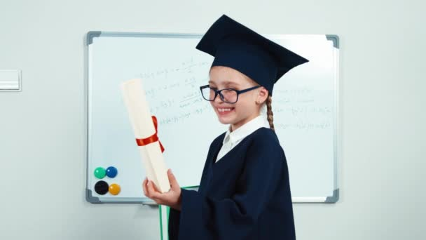 Graduate student 7-8 years in the mantle and hat. Child in glasses holding diploma and book. Girl smiling with teeth near whiteboard. Slider