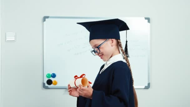 Cute student 7-8 years graduate in the mantle and hat holding diploma and laughing with teeth near whiteboard. Slider