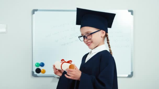 Cute student 7-8 years graduate in the mantle and hat. Child turns at camera with diploma in hands and smiling with teeth near whiteboard. Slider