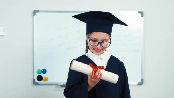Cute student 7-8 years graduate in the mantle and hat. Child looking at camera through diploma and smiling with teeth near whiteboard. Slider