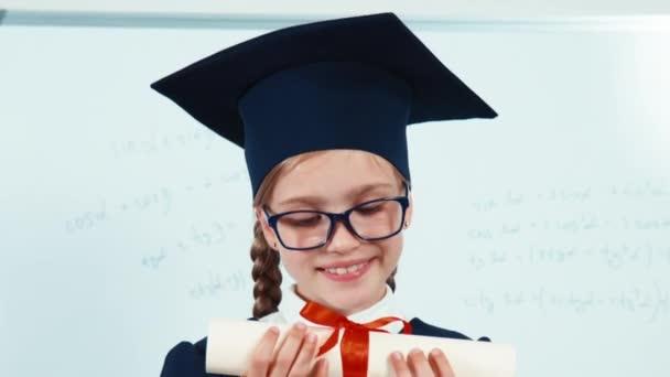 Zavřít portrétní studentka absolventky na svém plášti, zobrazující diplom a usmívat se pomocí zubů na kameře