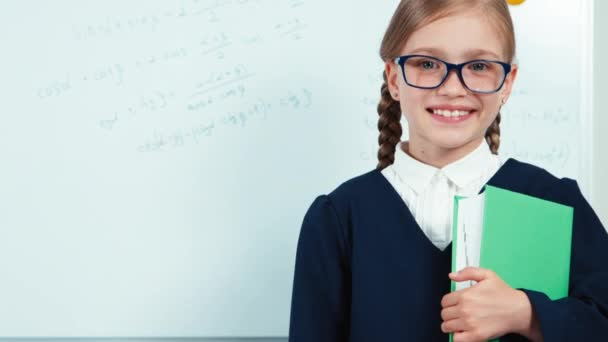 Close up portrait smiling little student girl graduate in the mantle holding book standing near whiteboard in the classroom